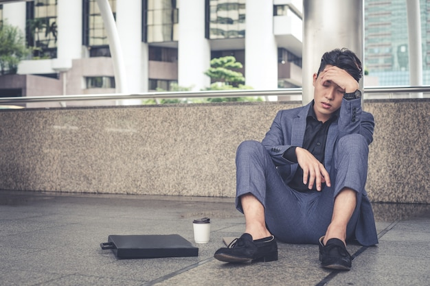 Depressed and tired businessman sitting at city