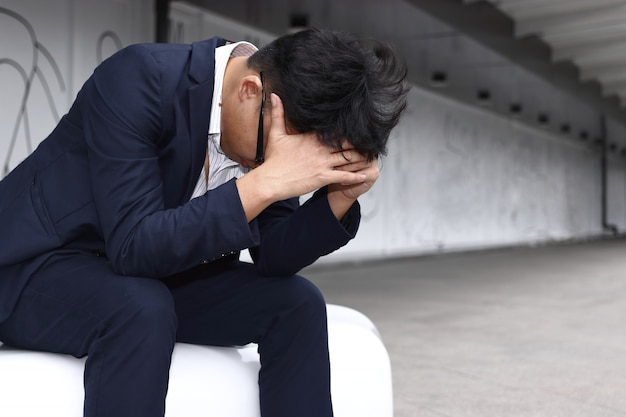Depressed tired young asian business man