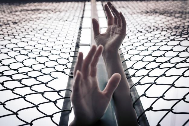 우울, 문제, 도움 및 기회. 희망이없는 여성들이 체인 링크 울타리 위로 손을 들어