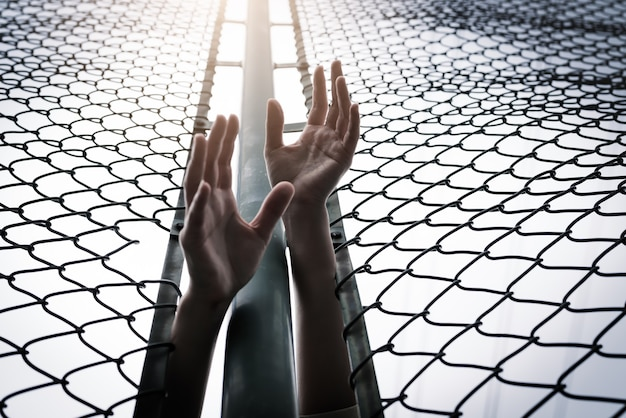 Depressed, trouble, help and chance. hopeless women raise hand over chain-link fence