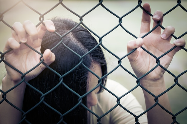 Depressed, trouble and solution. hopeless women hand on chain-link fence.