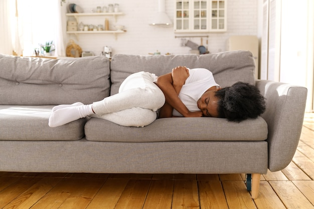Подавленная несчастная африканская женщина, лежащая на диване у себя дома, плачет, страдает от развода или расставания.