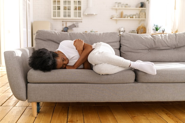 우울한 불행한 흑인 여성이 집에서 소파에 누워 울고, 이혼이나 헤어짐으로 고통받습니다.