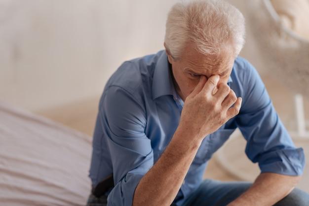 Подавленный несчастный пожилой мужчина наклоняется вперед и держится за переносицу, чувствуя себя несчастным