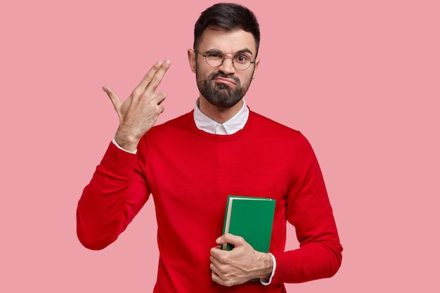Depressed unshaven male shoots himself in temple, frowns face with displeasure, carries green textbook, dressed in bright red clothes, models over pink space