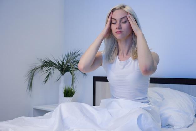 우울한 여자가 밤에 깨어, 그녀는 지치고 불면증으로 고통받습니다-image