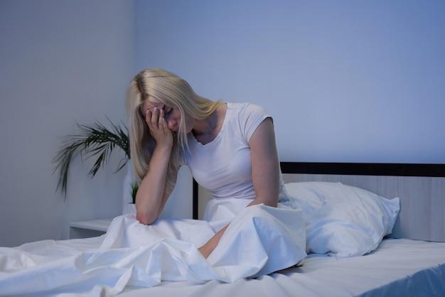 Подавленная женщина просыпается ночью, она истощена и страдает бессонницей
