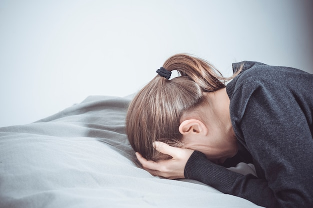 A depressed woman cries with her hands covering her face, lying on the couch.