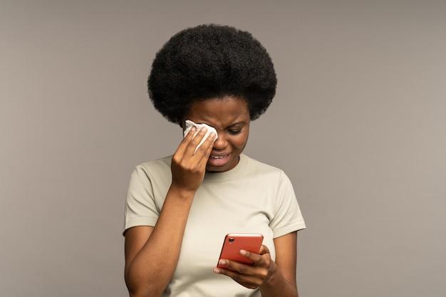 우울한 여자는 스마트폰으로 sms를 읽고 울며 휴대전화에서 흐느끼는 나쁜 소식이 있는 이별 메시지를 받습니다.