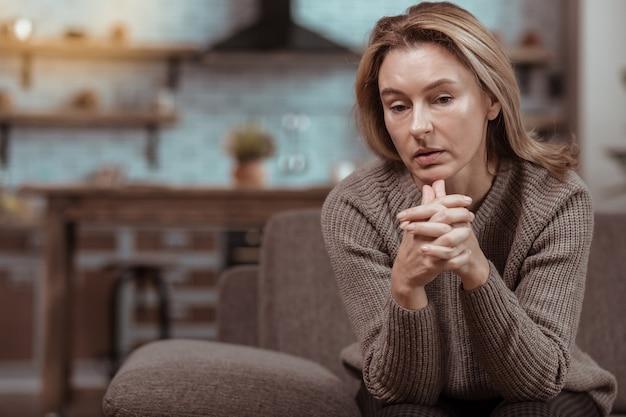 意気消沈した女性。夫の浮気を考えて落ち込んでいる暗い目の成熟した女性