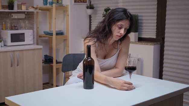 Depressed woman drinking a glass of wine alone in kitchen. unhappy person suffering of migraine, depression, disease and anxiety feeling exhausted with dizziness symptoms having alcoholism problems.