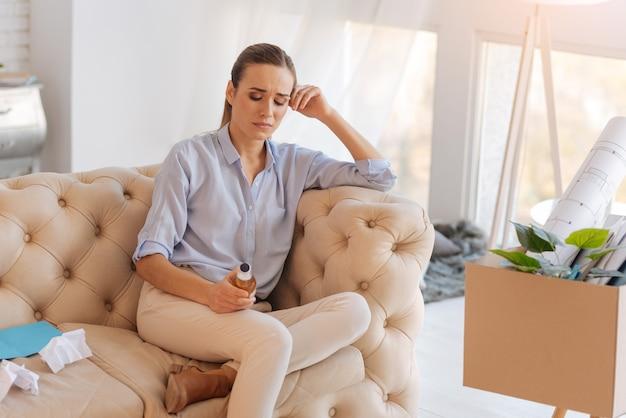 우울한 여자. 술의 도움으로 우울증을 극복하는 정서적 긴장된 실업자 여성과 멀지 않은 오래된 계획과 그래픽이 담긴 상자