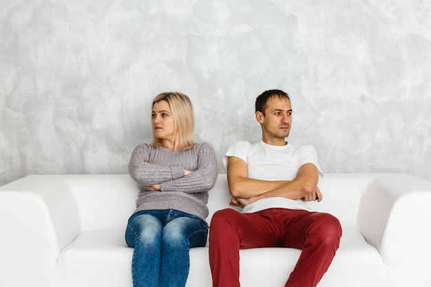 Depressed woman feeling offended and sad after fight with husband sitting on couch,