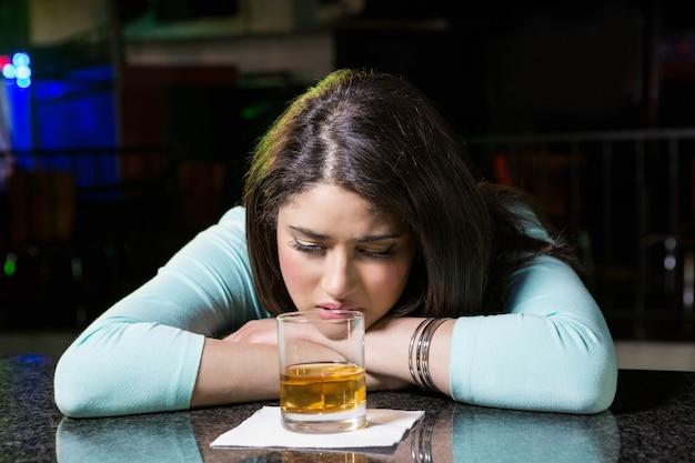 Depressed woman having whiskey at bar counter in bar