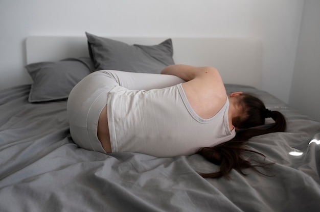 ベッドのフルショットで落ち込んでいる女性