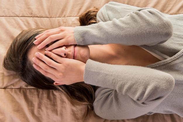 Подавленная женщина лежит на кровати