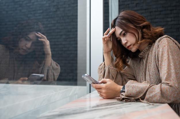 우울한 여자는 그녀의 스마트 폰을보고 두통을 가지고, 슬픈 느낌, 문제에 대해 걱정