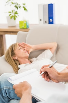 Depressed woman lying on couch and talking to therapist