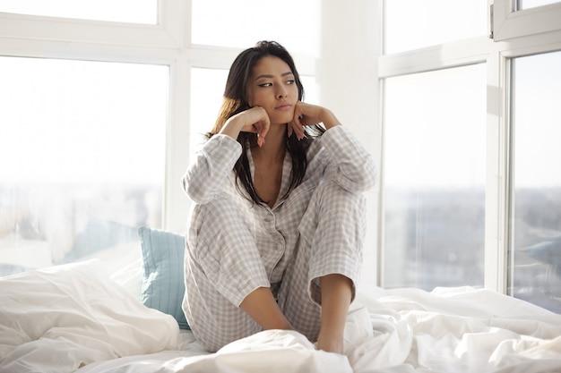 自宅のベッドで落ち込んでいる女性