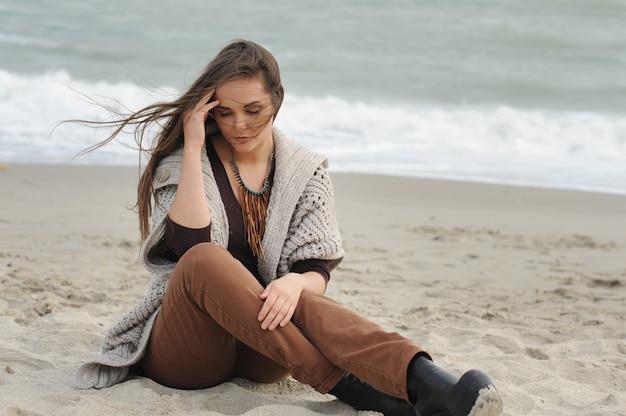 海のビーチに一人で座っている落ち込んでいる女性の肖像画