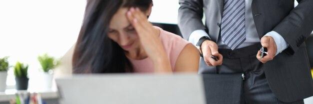 우울한 여자는 남자 스탠드 뒤에서 업무용 책상에 앉아 벨트를 풀고 있다