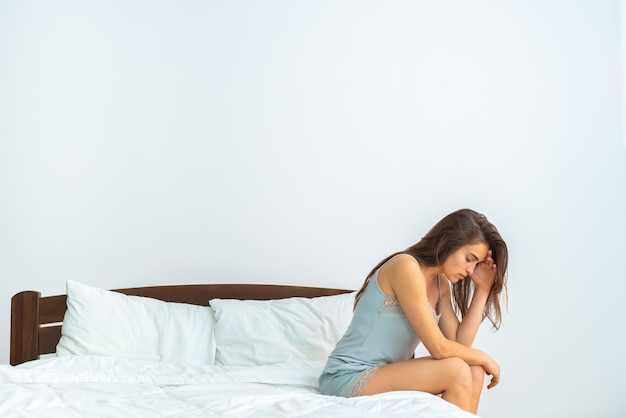 The depressed woman sitting on the bed on the white background