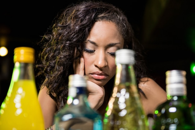 Depressed woman sitting at counter in bar