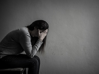 Depressed woman sitting on a chair in dark room at home.