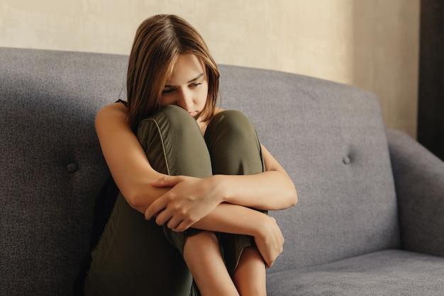 落ち込んでいる女性、ソファーに座って、自宅で動揺