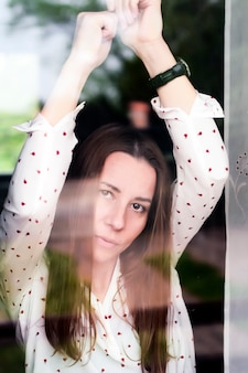 Depressed woman through the glass
