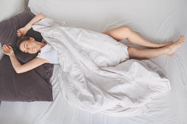 Depressed woman tormented by restless sleep, she is exhausted and suffering from insomnia, bad dreams or nightmares, psychological problems. inconvenient uncomfortable bed or mattress. lack of sleep