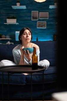 感情的な表現を持って泣いているテレビでドラマ映画を見ている落ち込んでいる女性