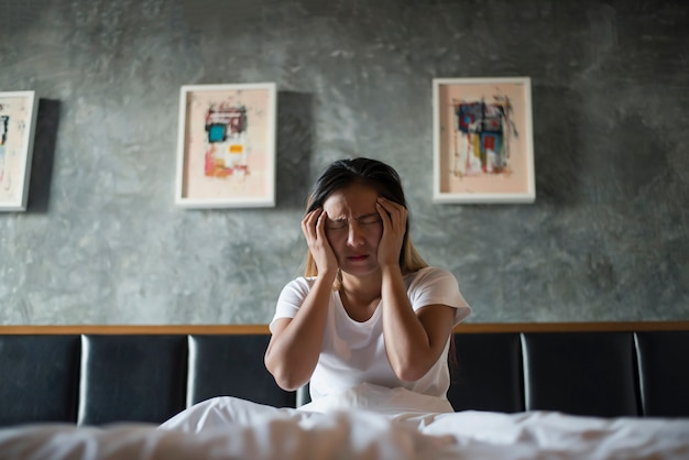 Donna depressa con mal di testa mano che tiene la testa sul letto