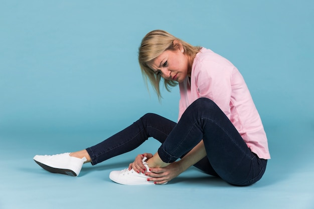 Depressed woman with injured foot sitting on blue background
