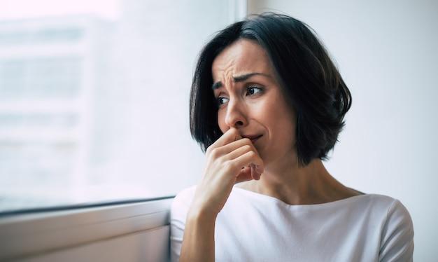 Подавленная женщина с короткой стрижкой, которая плачет, касаясь ее лица. девушка, которая кричит с закрытыми глазами из-за своего психического заболевания.