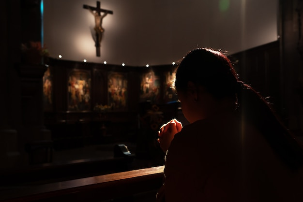 Depressed women sitting in the low light church and praying to jesus on the cross, international human rights day concept