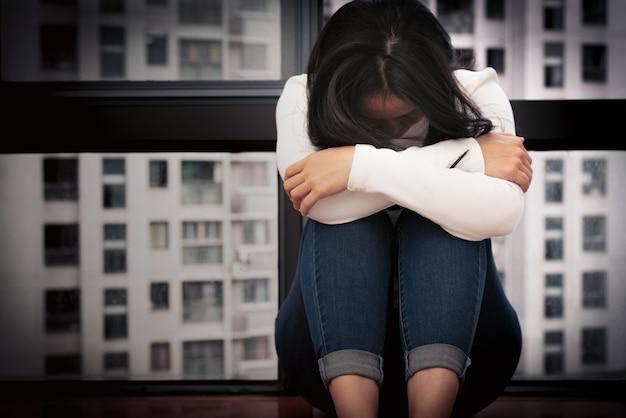 Depressed women sitting near window, alone, sadness, emotional concept