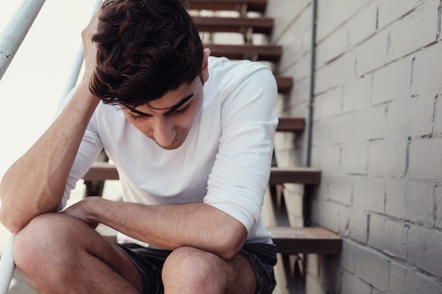 Depressed young adult man sitting alone, mental health concept