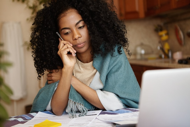 Подавленная депрессия молодая африканская женщина, не способная оплачивать счета за газ и электричество, разговаривает по мобильному телефону, недовольна решением банка не продлевать срок кредита. финансовая проблема и экономический кризис