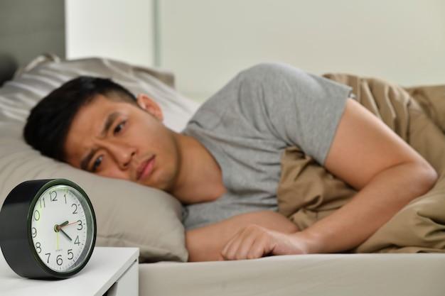 침대에 누워 있는 우울한 젊은 아시아 남성은 불면증으로 잠을 잘 수 없으며 알람 시계에 집중합니다