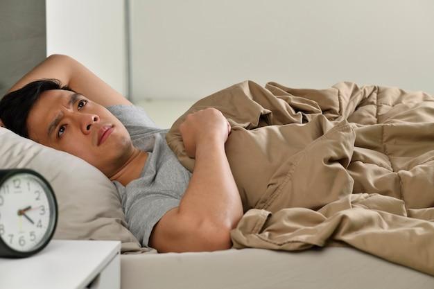 침대에 누워 우울한 젊은 아시아 남자 불면증에서 잠을 잘 수 없습니다