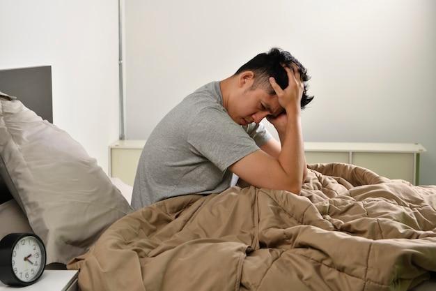침대에 앉아 우울한 젊은 아시아 남자 불면증에서 잠을 잘 수 없습니다