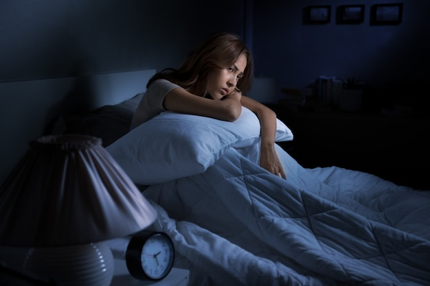 Depressed young asian woman sitting in bed cannot sleep from insomnia
