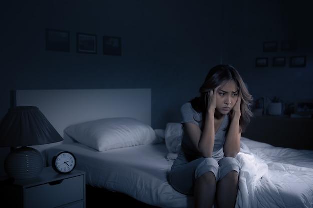 침대에 앉아 우울한 젊은 아시아 여성은 불면증으로 잠을 잘 수 없습니다