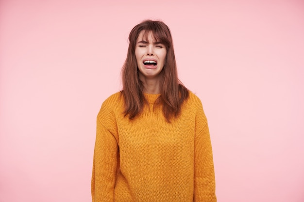 Depressed young brunette female frowning her face with closed eyes while crying sadly with opened mouth, wearing mustard woolen sweater while posing over pink wall