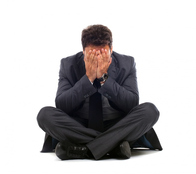 Depressed young businessman sitting on the ground