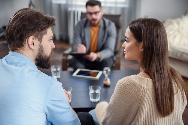 Depressed young couple of man and woman speaking with psychologist on therapy session in modern office. bad relationships without future.