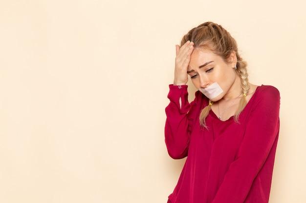 結ばれた口と赤いシャツで落ち込んでいる若い女性