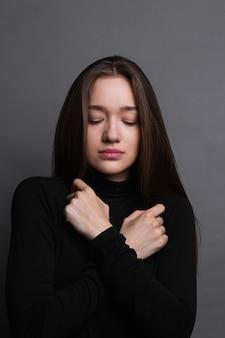 落ち込んでいる若い女の子。暗い灰色の背景に黒のシャツで悲しい若い女性