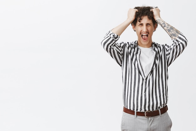 Giovane depresso con i baffi in camicia a righe che perde la pazienza urlando ad alta voce tirandosi fuori i capelli dalla testa stufo e incazzato da uno stupido capo in posa su un muro grigio